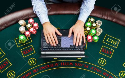 casino, online gambling, technology, people concept - close up of poker player with playing cards, laptop, chips at green casino table